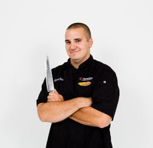 Chef Aaron with a black uniform holding a kitchenknife